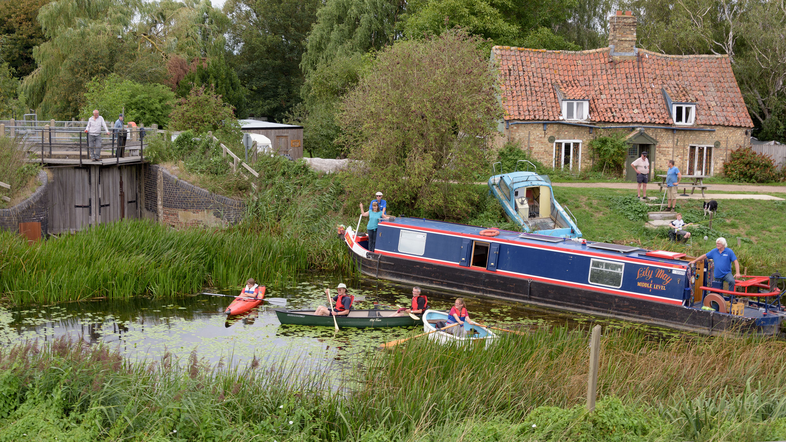 a narrowboat and canoes rally by the closed Welches Dam Lock